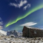 northern-lights-over-a-small-wooden-house-flakstad